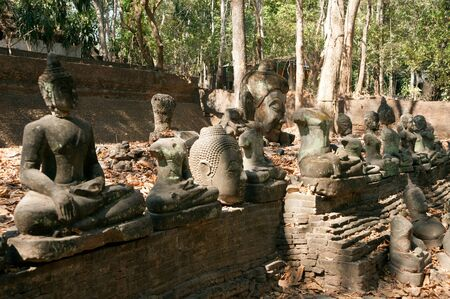 disintegrate: Ancient outdoor Buddhas field of broken sculpture in Wat Umong Suan Puthatham. in Chiang Mai city,Thailand.