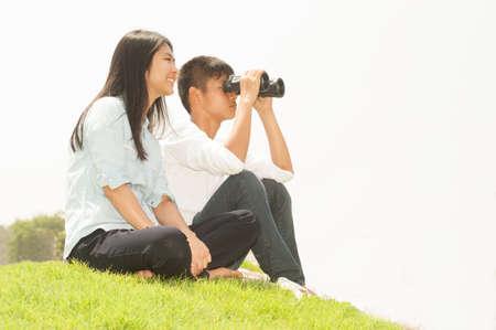 using binoculars: Asian young boy and girl sitting on grass using binoculars . Stock Photo