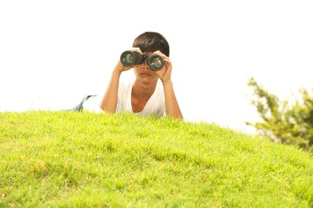 using binoculars: Asian young boy lying on grass using binoculars.