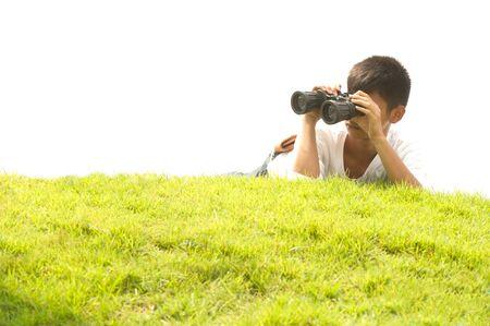 using binoculars: Asian young boy lying on grass using binoculars.