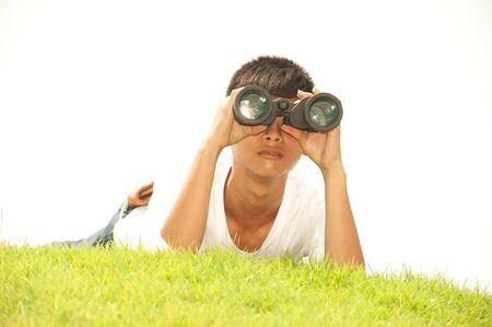 using binoculars: Asian young boy lying on grass using binoculars .