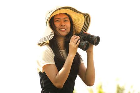 using binoculars: Pretty Asian young woman using Binoculars .