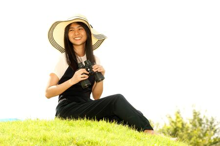 using binoculars: Pretty Asian young  woman sitting on grass using binoculars . Stock Photo