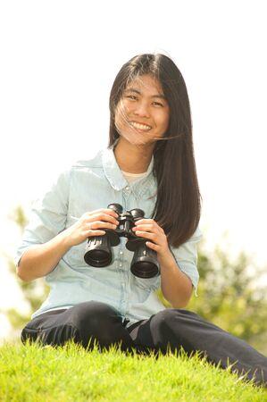 using binoculars: Pretty Asian young  woman sitting on grass using binoculars . Stock Photo