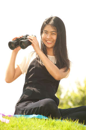 using binoculars: Pretty Asian young  woman sitting on grass using binoculars smiling.
