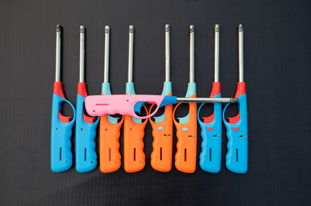 butane: Group of colorful Gas lighter gun for gas-stove on a black background.