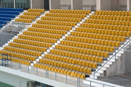 Yellow color of stadium seats in background. Stock Photo