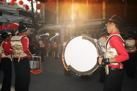 cerebrate: Marching in a parade during Chinese New Year Festival.