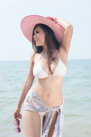 Pretty Asian woman posing relax on the beach with pink hat.