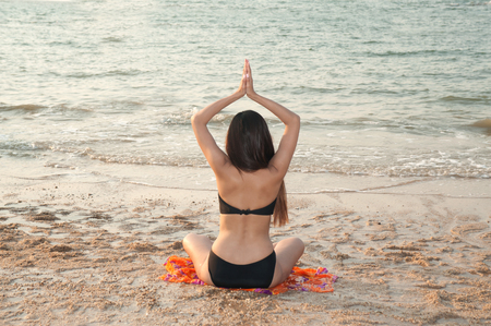 Pretty woman sitting in fitness yoga exercise on the beach. Stock Photo
