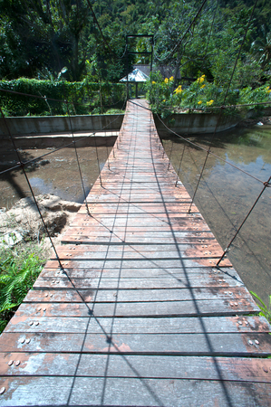Wire hanging bridge with wooden pathway in Thailand. Stock Photo