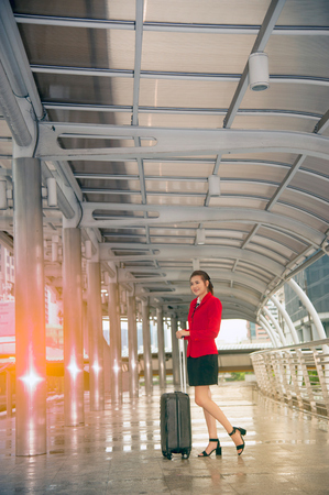 portmanteau: Asian pretty business woman standing with luggage at crossing bridge landmark in Bangkok . Stock Photo