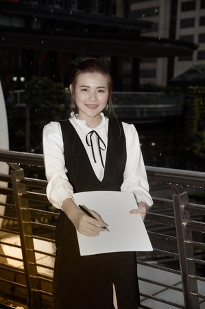 Asian Pretty woman in black dress writing document stand on crossing bridge landmark of Bangkok.