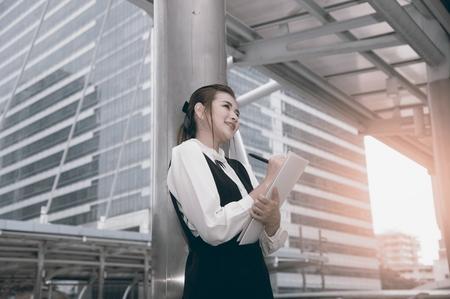 Asian Pretty woman in black dress writing document stand on crossing bridge landmark of Bangkok.