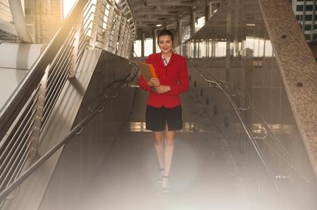 Asian Pretty woman in red suit holding document walking on crossing bridge landmark of Bangkok.