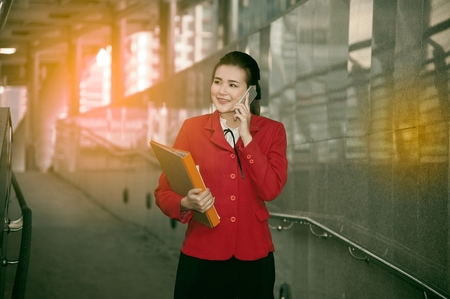 Asian Pretty woman in red suit holding document and use smart phone walking on crossing bridge landmark of Bangkok. Stock Photo