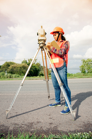 Weiblicher Landvermesser oder Ingenieur, die Maß auf der Autobahn machen. Standard-Bild