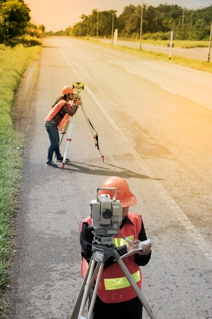 topografo: Surveyor or Engineer making measure with partner on the highway.