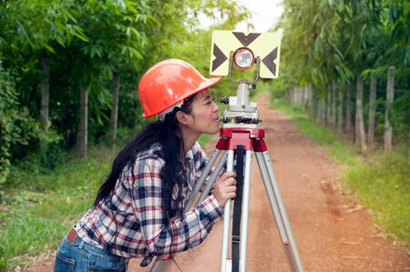 reflectors: Female Surveyor or Engineer making measure by prism reflector on the street in a field. Stock Photo