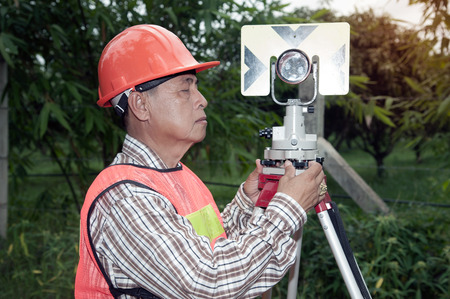 Surveyor or Engineer making measure by prism reflector in a field.