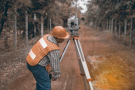 Surveyor or Engineer making measure by Theodolite on the street in a field.