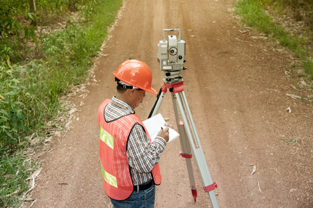 reflectors: Surveyor or Engineer making measure by Theodolite on the street in a field.