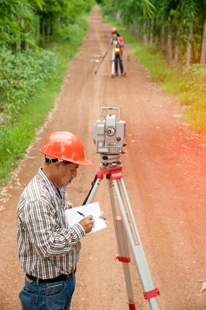 reflectors: Surveyor or Engineer making measure by Theodolite with partner on the street in a field.