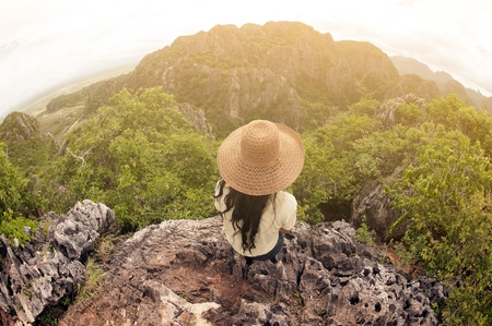 Happy female traveler with hat sitting on top of a mountain and enjoying viewpoint of Thailand.-