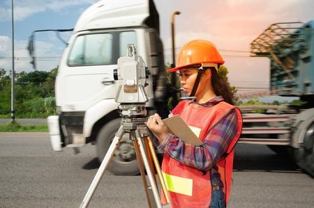 theodolite: Female Surveyor or Engineer making measure by Theodolite on the highway.