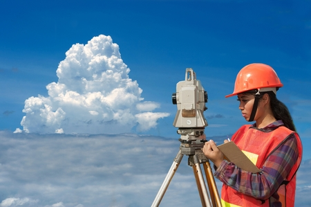 Female Surveyor or Engineer making measure by Theodolite on the field with sky background.