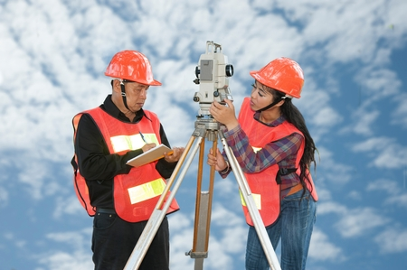 theodolite: Surveyor or Engineer making measure by Theodolite on the field with sky background.