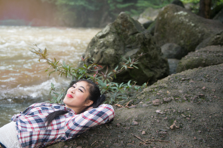 Happy female lying on a rock of waterfall and freedom