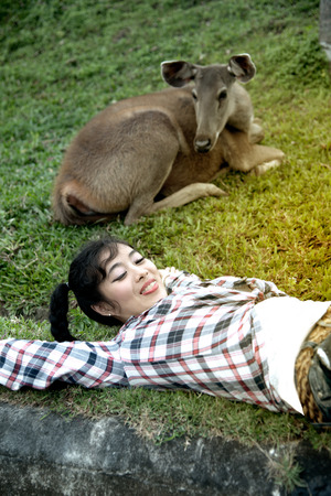 Beautiful smiling Asian woman lying down and emulate deer .