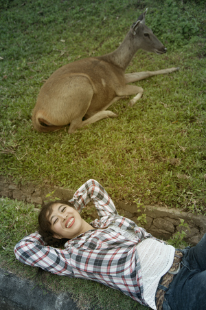 Beautiful smiling Asian woman lying down and emulate deer. Stock Photo