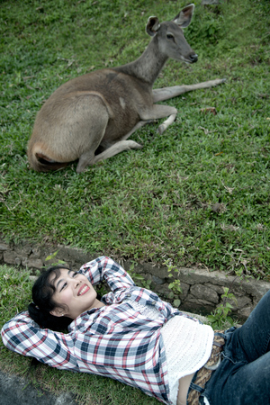 par: Beautiful smiling Asian woman lying down and emulate deer. Imagens