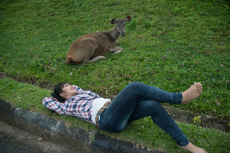 Beautiful smiling Asian woman lying down and emulate deer. Stock Photo