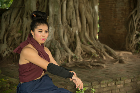 Pretty Asian woman posing in Thai ancient warriors at Gate of time of Wat Phra Ngam in Ayutthaya Historical Park ,Thailand.