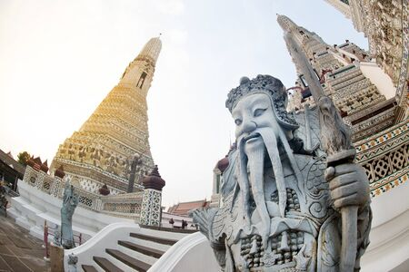 Day time of Chinese guardian statue at main Prang of Wat Arun Ratchawararam temple ,Bangkok,Thailand. Banco de Imagens