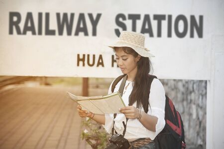 Pretty Asian female traveler looking map and waiting train at railway station in Thailand.