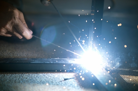 The worker is welding sparks table steel in factory.
