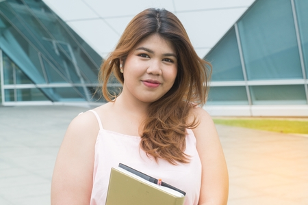 Portrait of Asian pretty smiley face fat woman pose and holding booklet front of building. Banco de Imagens