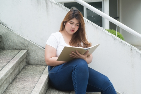 Portrait of Pretty Asian smiley fat woman sit and thinking at staircase of building.
