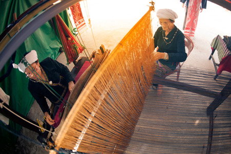 PHAYAO,THAILAND-MAY 9,2015 : Unidentified Tai Lue minority senior woman is a demonstrate to procedure making Thai cotton weaving showing in 8th Ethnic amazing festival at Chiangkum District , Phayao Province , Thailand.