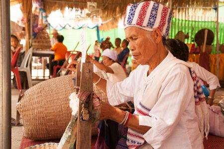 PHAYAO, THAILAND - MAY 9, 2015 : Unidentified senior Tai Lue minority woman is a spinning traditional cotton yarn treads by ancient rolling machine made of wood showing in 8th Ethnic amazing festival.
