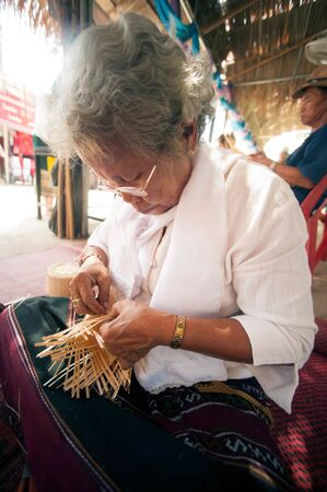 PHAYAO, THAILAND - MAY 9, 2015 : Unidentified senior Tai Lue minority woman made a tradition woven bamboo container for steamed cooked glutinous rice with her hand showing in 8th Ethnic amazing festival.