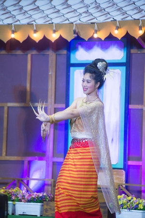 The lady in Middle Thai classical dancing suit is showing pattern of traditional dancing on platform. Reklamní fotografie