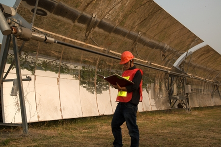 The worker in uniform and helmet checks Solar Parabolic Troughs.