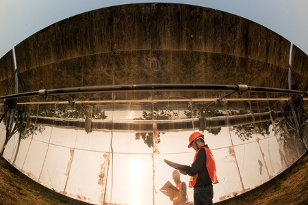 The worker in uniform and helmet checks Solar Parabolic Troughs. Foto de archivo