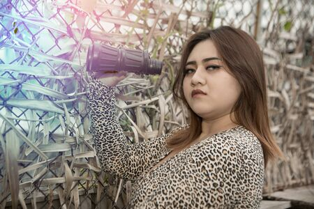 Asian plus size sexy , fat and overweight long hair model female in dresses pose hold a Binoculars.