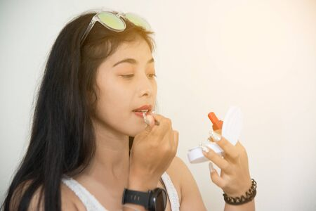 Portrait of pretty Asian woman applies red lipstick . Hand of make-up master, painting lips of young beauty model girl . Make up in process.
